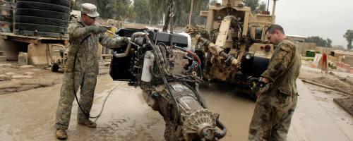 Army Mechanics cleaining a power unit